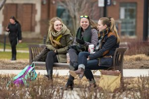 A group of friends talking and laughing near the sundial on Jan. 17, 2017. (Sean Flynn/UConn Photo)
