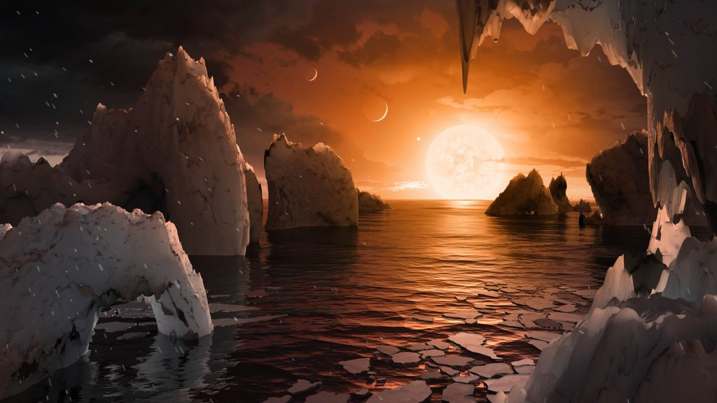 This artist's concept allows us to imagine what it would be like to stand on the surface of the exoplanet TRAPPIST-1f, located in the TRAPPIST-1 system in the constellation Aquarius. Because this planet is thought to be tidally locked to its star, meaning the same face of the planet is always pointed at the star, there would be a region called the terminator that perpetually divides day and night. If the night side is icy, the day side might give way to liquid water in the area where sufficient starlight hits the surface. One of the unusual features of TRAPPIST-1 planets is how close they are to each other -- so close that other planets could be visible in the sky from the surface of each one. In this view, the planets in the sky correspond to TRAPPIST1e (top left crescent), d (middle crescent), and c (bright dot to the lower right of the crescents). TRAPPIST-1e would appear about the same size as the moon and TRAPPIST1-c is on the far side of the star. The star itself, an ultra-cool dwarf, would appear about three times larger than our own sun does in Earth's skies. (NASA Image)