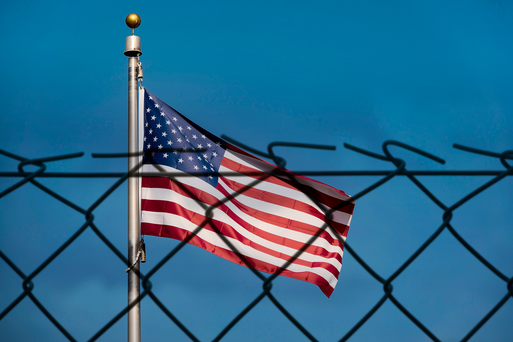 American flag and fence. (Alxey Pnferov via Getty Images)