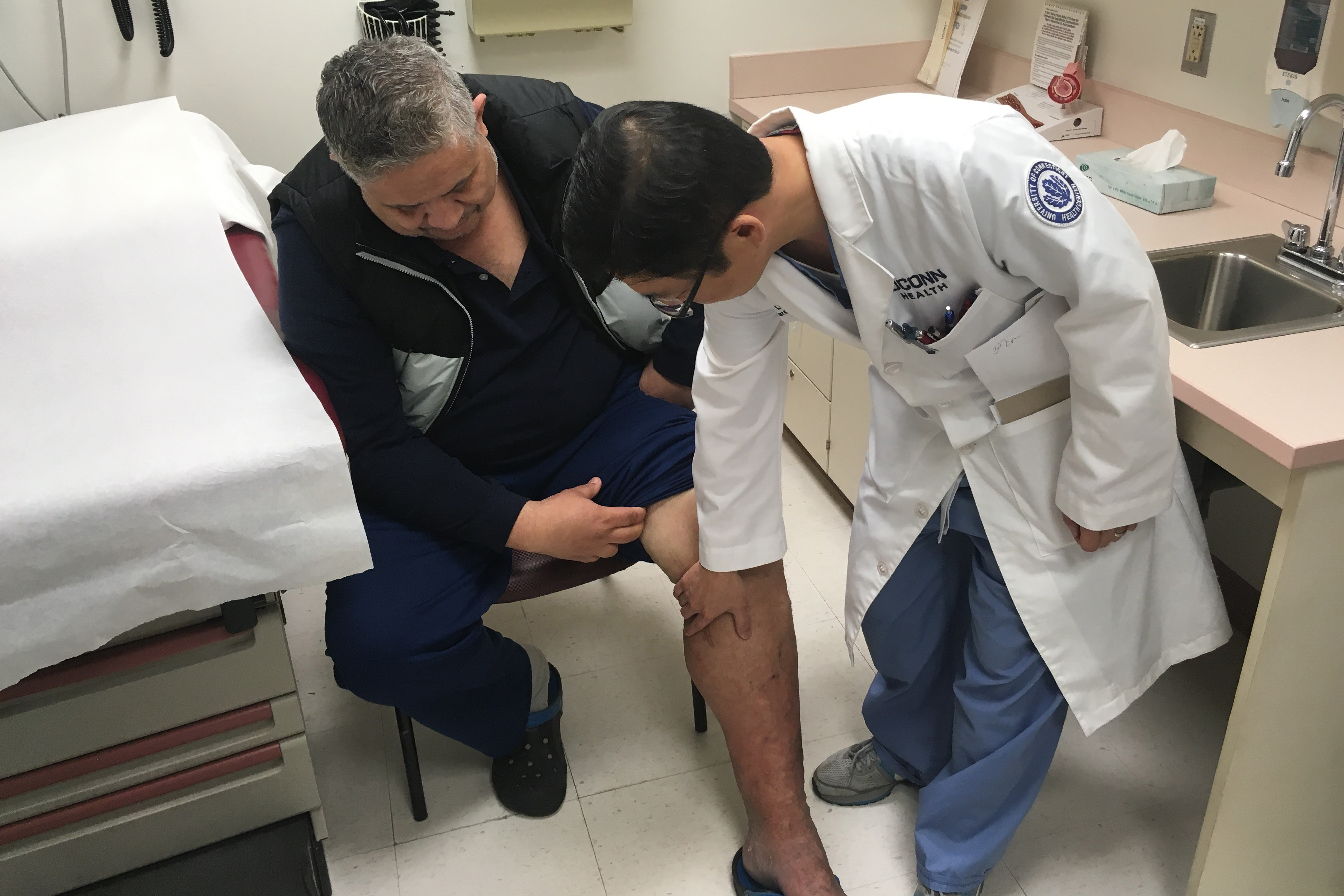 50 year-old Eliseo Bonilla, seated, with his UConn Health cardiologist Dr. JuYong Lee. (Lauren Woods/UConn Health Photo)