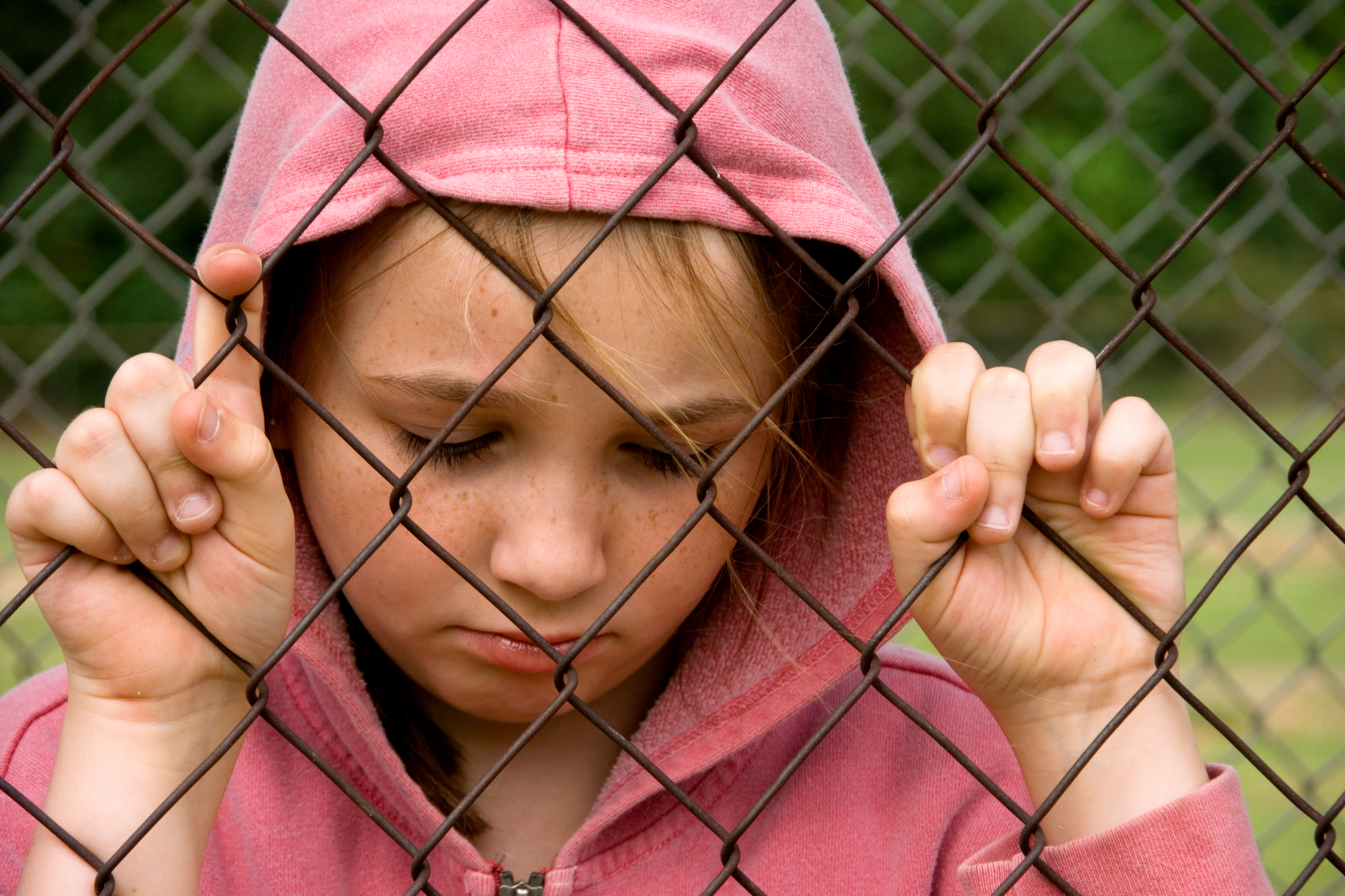 Unhappy girl behind a fence. (Getty Images)