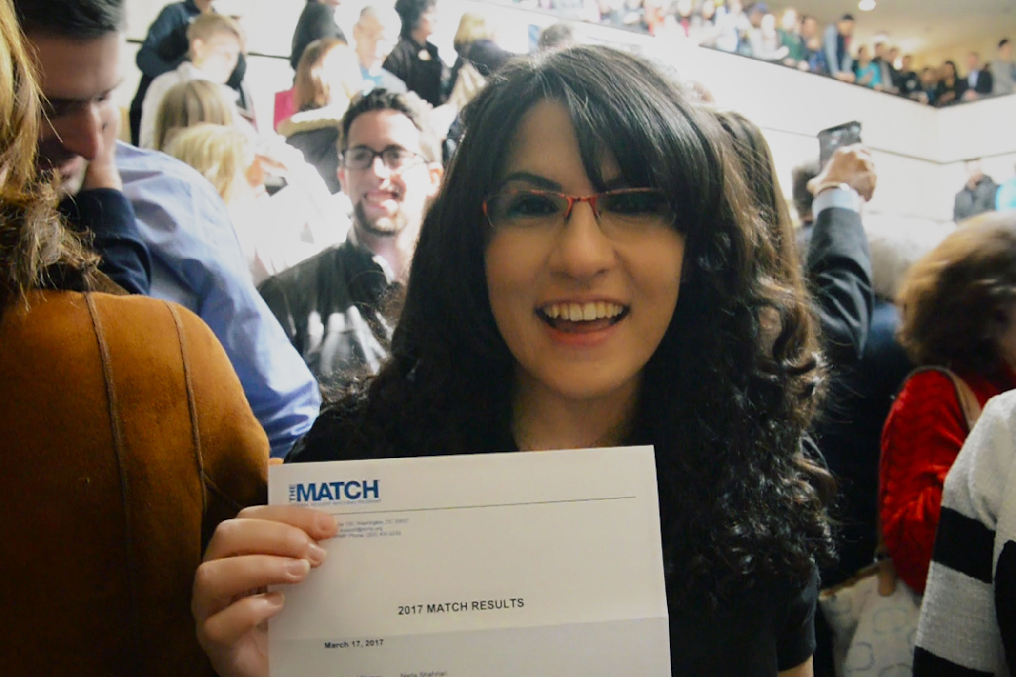 Neda Shahriari displays the letter informing her that she will do her dermatology training at her first-choice placement – UConn Health. (Bret Eckhardt/UConn Photo)