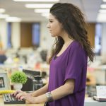 Woman standing at her office desk. (Getty Images)