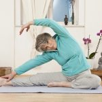 A senior woman stretching at a yoga studio. (Getty Images)