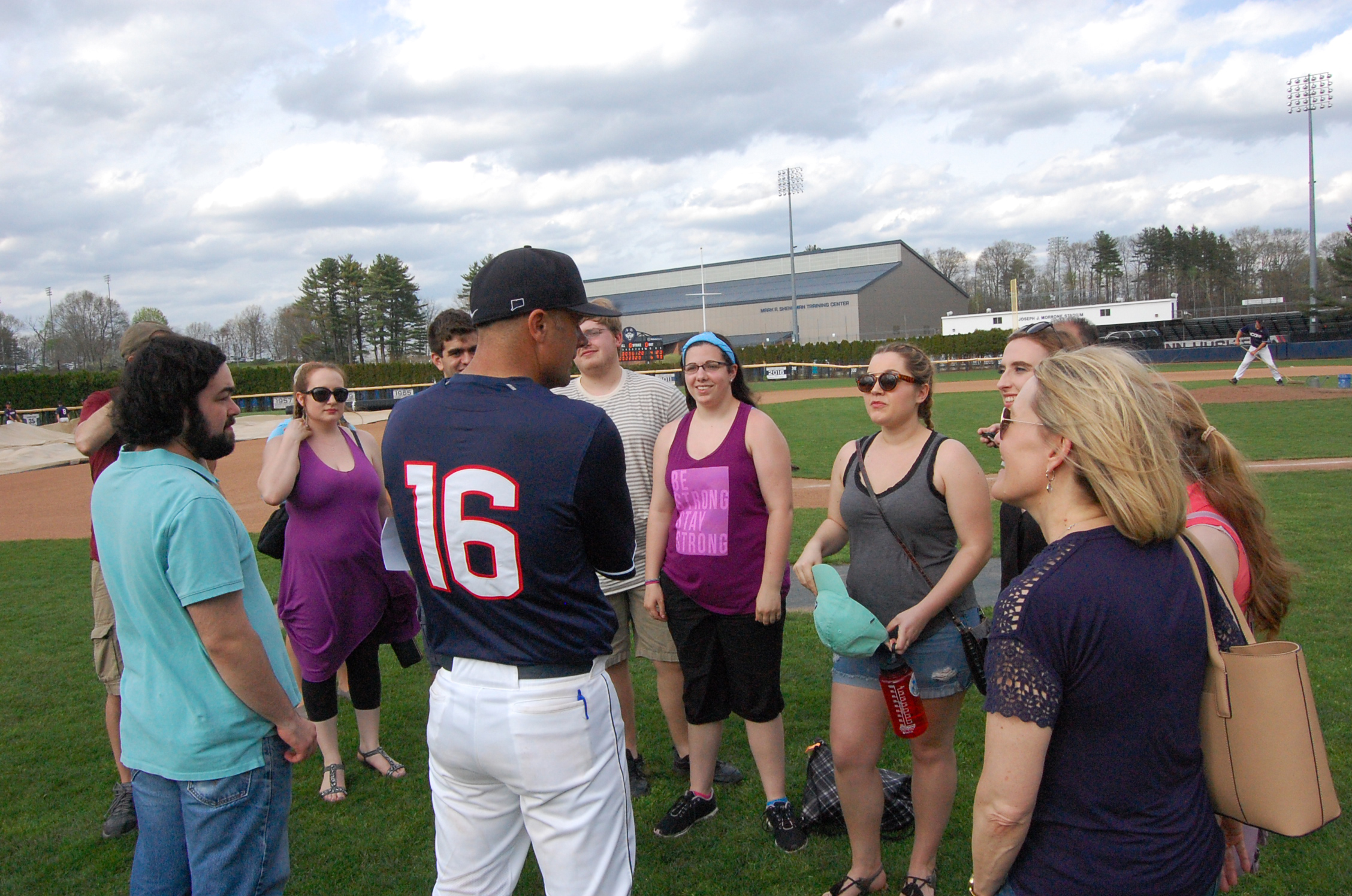 "Head baseball coach Jim Penders '94 (CLAS), '98 MA, speaks with undergraduate and graduate music students who performed in ""H.M.S. Pinafore"" following the Huskies' win over Cincinnati on April 30. (Kenneth Best/UConn Photo)"