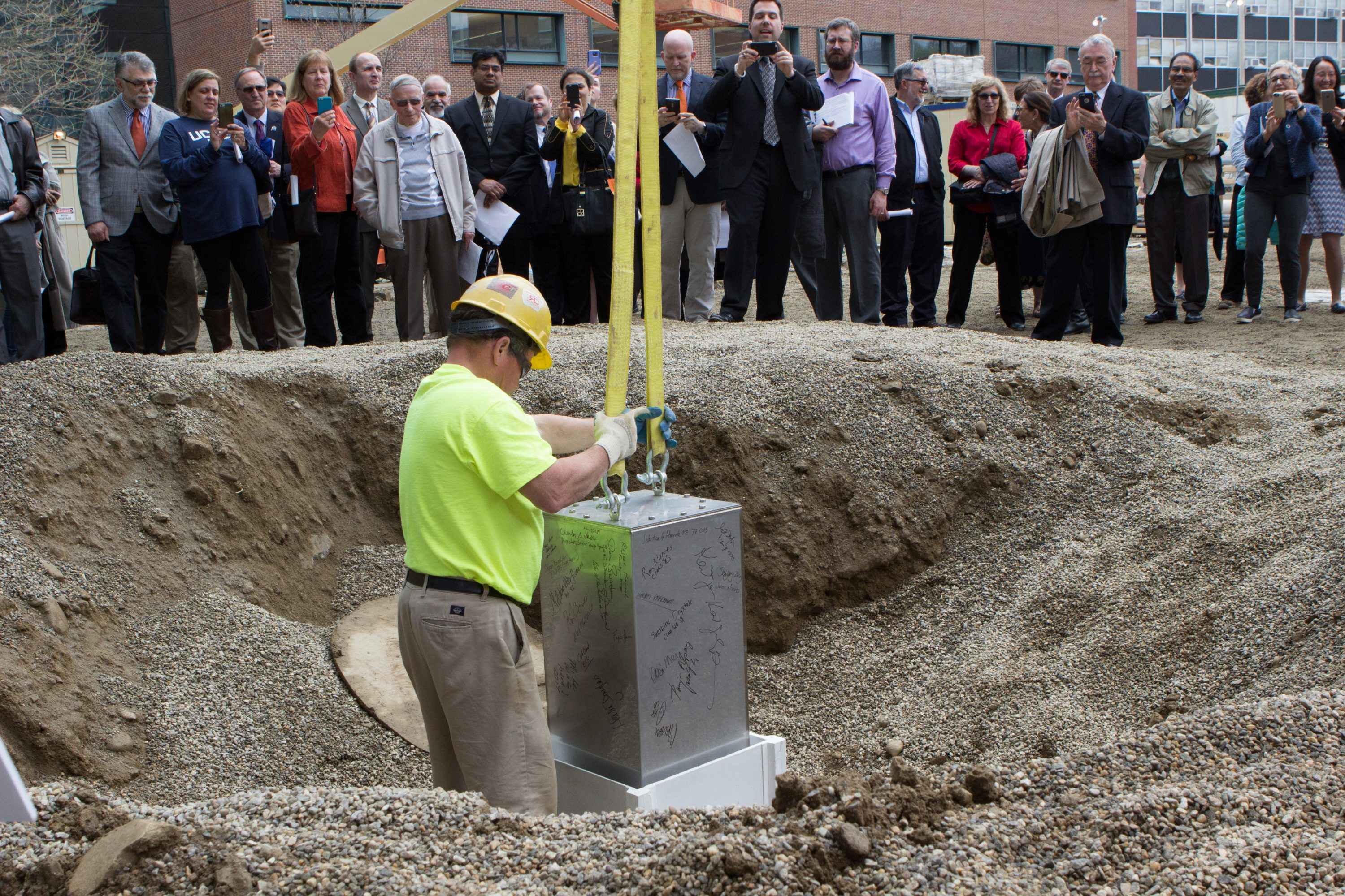 A construction worker lowers the time capsule into an ultra-high performance, fiber-reinforced concrete vault that will hold it for the next 100 years. (Christopher LaRosa/UConn Photo)