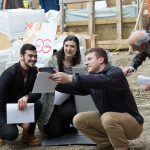 From left Jason Vafiades '17 (ENG), Phoebe Szarek '17 (ENG), and  Emil Atz '17 (ENG) take a selfie with the time capsule. Also shown (wearing an orange shirt) is Peter Glaude, senior machine shop engineer. (Christopher LaRosa/UConn Photo)
