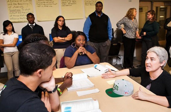 Leslie Blatteau, a world history teacher, right, and Steve Staysniak, an English teacher, work with high school seniors at Metropolitan Business Academy in New Haven as part of High Need School Grant from the Connecticut Writing Project.