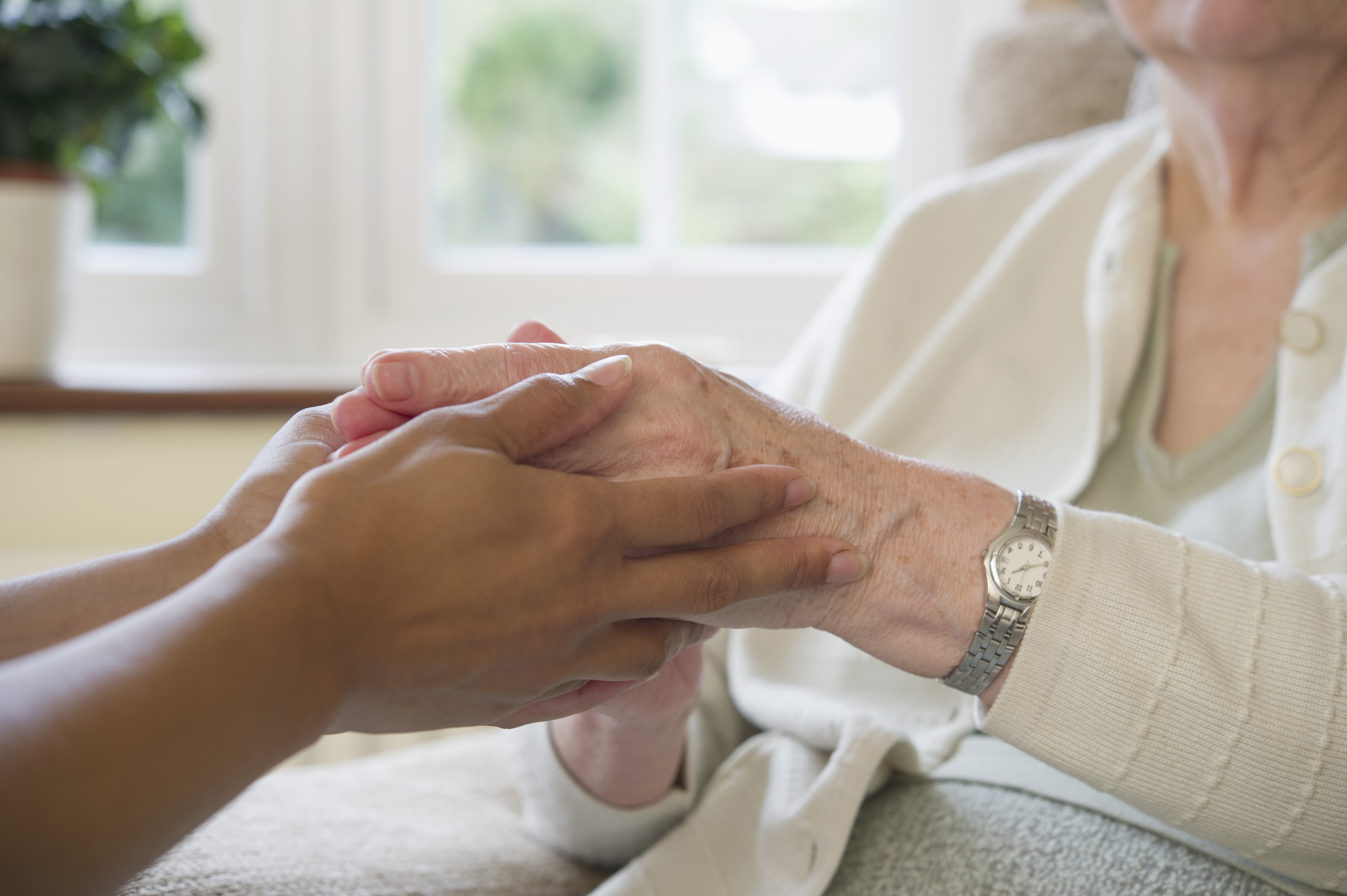 Close up of older woman and home caretaker holding hands. (Getty Images)