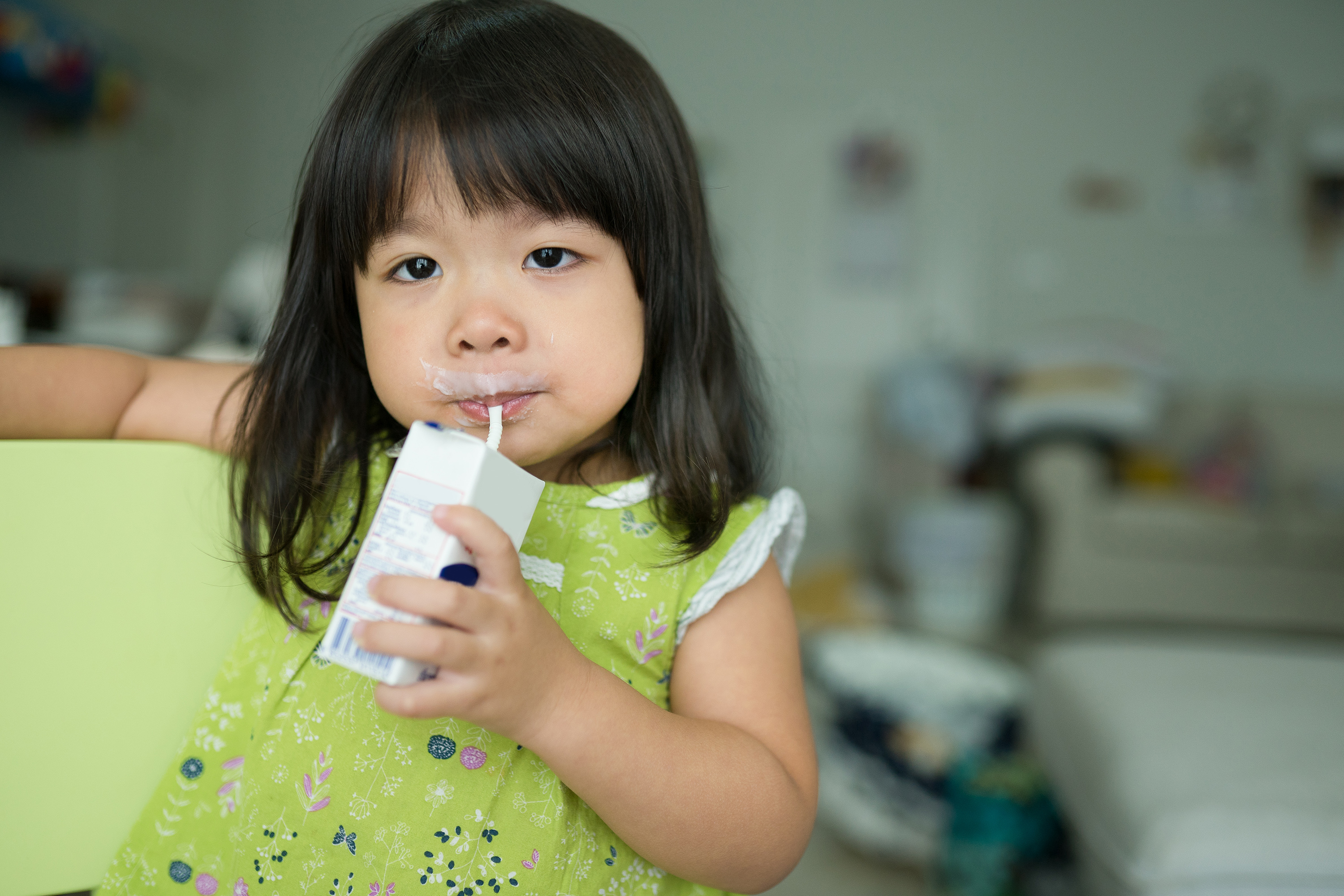 A child drinking a small carton of milk. (Shutterstock)