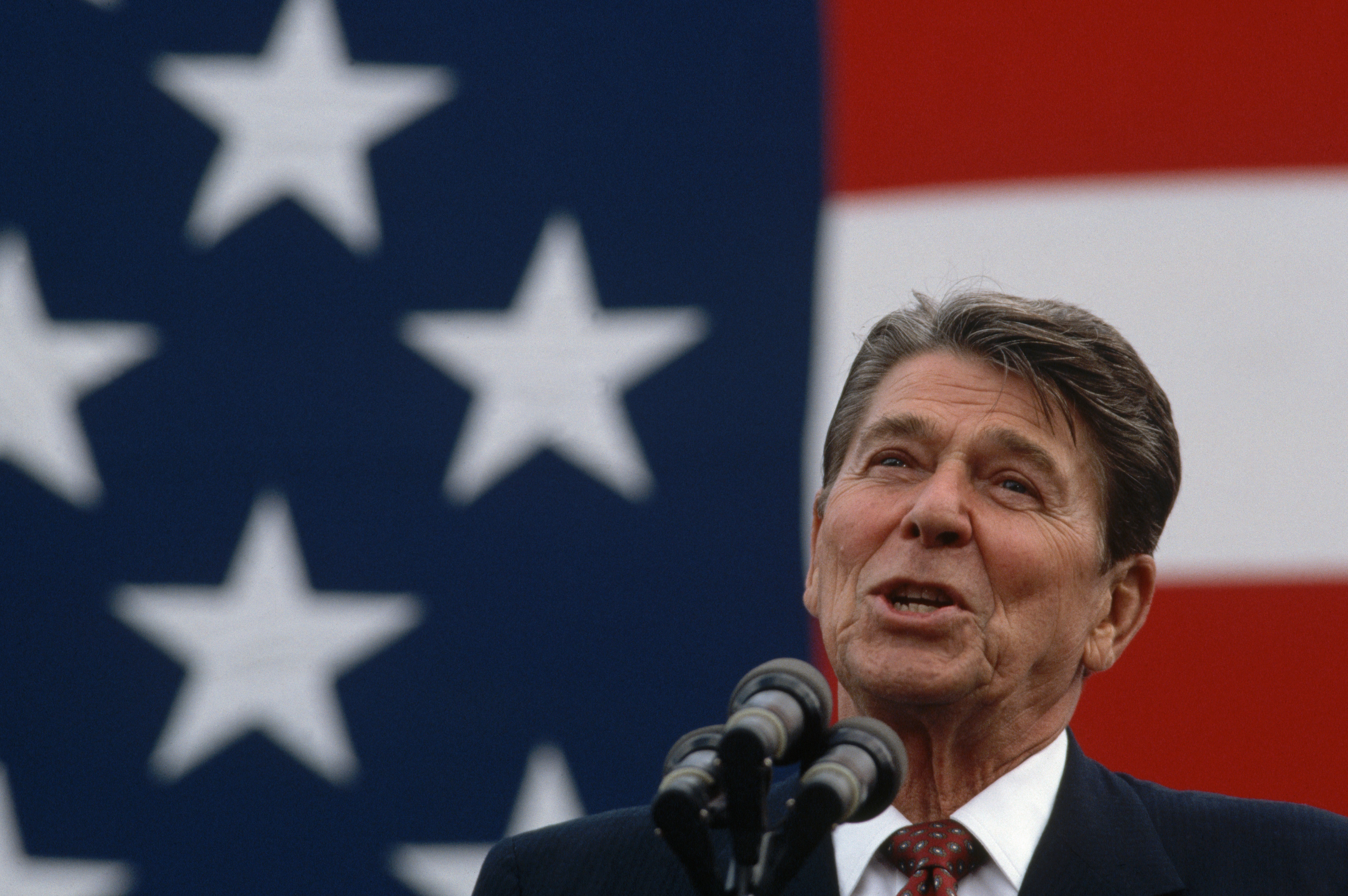 President Ronald Reagan makes a stump speech in front of a large American flag. (Photo by Wally McNamee/CORBIS via Getty Images)