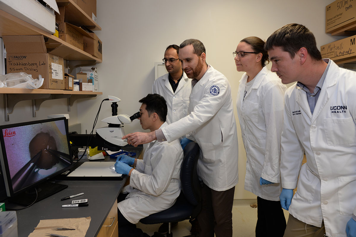 Guided by Ephraim Trakhtenberg, postdoctoral fellow Juhwan Kim demonstrates microscope-assisted surgery to master's student Muhammad Sajid (background), undergrad Kathleen Renna, and M.D.-Ph.D. student Bruce Rheaume. (Photo by Ethan Giorgetti)