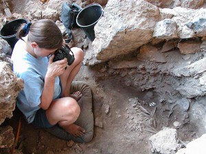 <p>Natalie Munro, associate professor of anthropology, photographing a grave thought to be that of a shaman at the archaeological site of Hilazon Tachtit Cave in northern Israel. Photo by Gideon Hartman</p>