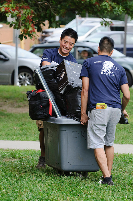 <p>Husky Haulers Thomas Wong, a junior and David Zeng, a senior,  help a new student move into the North Campus Residence Complex. Photo by Peter Morenus</p>