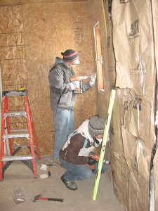Bryan Banville, standing, a UConn student, and Kimberly Burfield of James Madison University, work at Bob Bear Killer's house on Pine Ridge Indian Reservation during spring break. Photo by Lauren Young