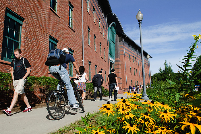 <p>Students pass by the Chemistry Building, beside a patch of Black-Eyed Susans in bloom. Photo by Peter Morenus</p>