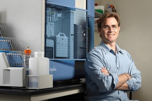 <p>Brenton Graveley, associate professor of genetics and developmental biology, with the Illumina Genome Analyzer, a new instrument for sequencing genetic material. Photo by Lanny Nagler</p>