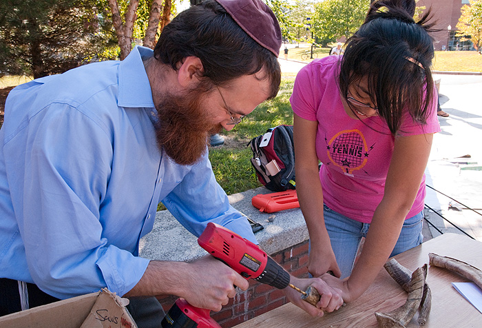 <p>Rabbi Shlomo Hecht, director of UConn Chabad, helps senior Wenhui Sun create a shofar in preparation for the Jewish celebration of Rosh Hashanah. The shofar is an instrument carved out of the horn of a ram. Photo by Frank Dahlmeyer</p>