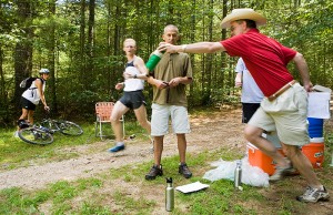 <p>Physical therapy professor Craig Denegar hands a drink to a runner during a dehydration study, as kinesiology professor Doug Casa looks on. Photo by Sean Flynn</p>
