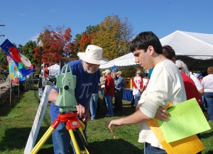 <p>Thomas Meyer, associate professor of natural resources and the environment, explains the workings of a 'total station,' a piece of equipment used in surveying, to participants in the Cornucopia Challenge scavenger hunt. Photo by Susan Schadt</p>