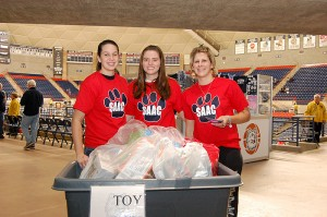 <p>A holiday toy drive at Gampel Pavilion during a basketball game, with Softball team members, from left, Brittany Duclos, Megan Apper, and Dana Hughes. Photo by Ken Best</p>