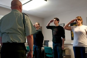 <p>Sergeant First Class John Maynard demonstrates various military conventions to help students, from left, Bryan Swormstedt, Daniel Seigerman, and Cayla Buettner prepare for an upcoming Connecticut Repertory Theatre production. Photo by Frank Dahlmeyer</p>