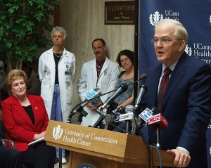 <p>President Michael Hogan comments on the new plan for the Health Center, as Gov. M. Jodi Rell and Health Center employees and supporters look on. Photo by Chris DeFrancesco</p>