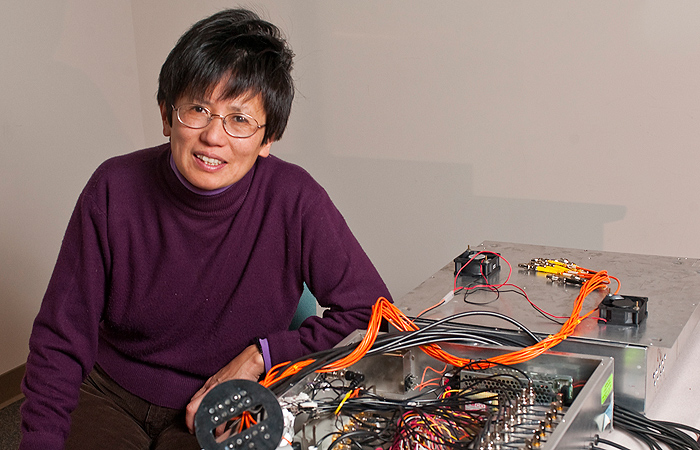 <p>Qing Zhu, professor of electrical and computer and engineering, with her device for early detection of breast cancer lesions. Photo by Peter Morenus.</p>