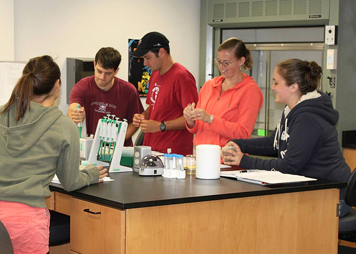 <p>Under the direction of plant sciences professor Gerald Berkowitz, Camp DNA students use current molecular techniques, such as gel electrophoresis and polymerase chain reactions (PCR), to isolate, replicate and observe mutations to DNA in the laboratory. Shown in this photo (L to R) are Jonathan Glenn, Greg Tutolo, Emily Kieswetter, and Danielle Jeffries.  Tutolo is a teacher at E.O. Smith HS. Photo by Cameron Faustman.</p>