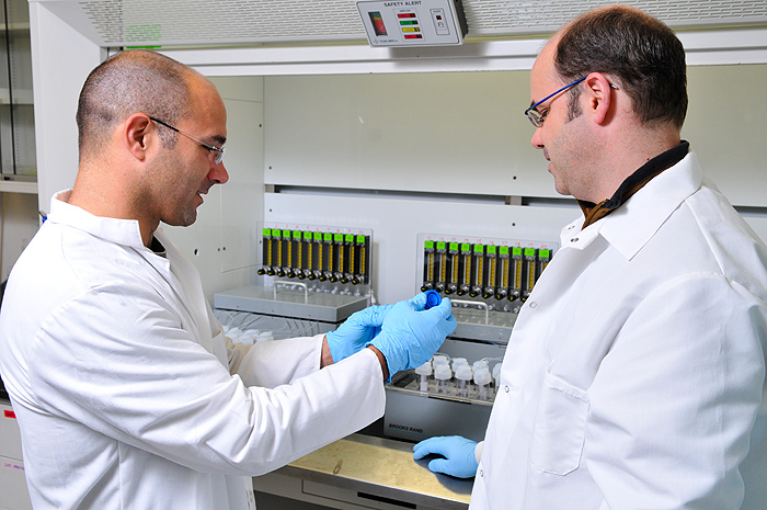 <p>From left: Joe Bushey, assistant professor of Civil and Environmental Engineering and Chris Perkins, lab director of the Center for Environmental Sciences and Engineering work with water samples in their lab. Photo by Jessica Tommaselli</p>