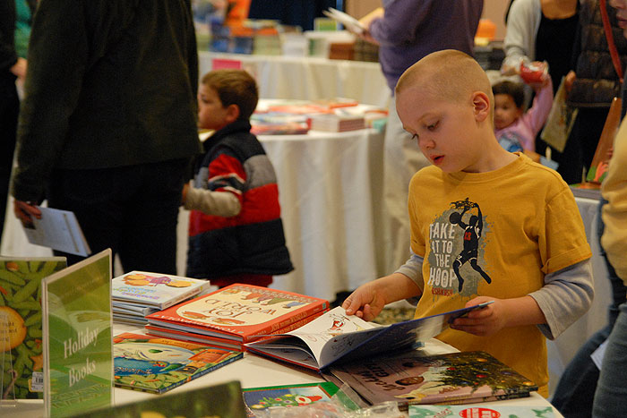<p>A child is captivated by words and pictures at the Connecticut Children's  Book Fair held in the Rome Ballroom on November 13. Photo by Ariel Dowski</p>
