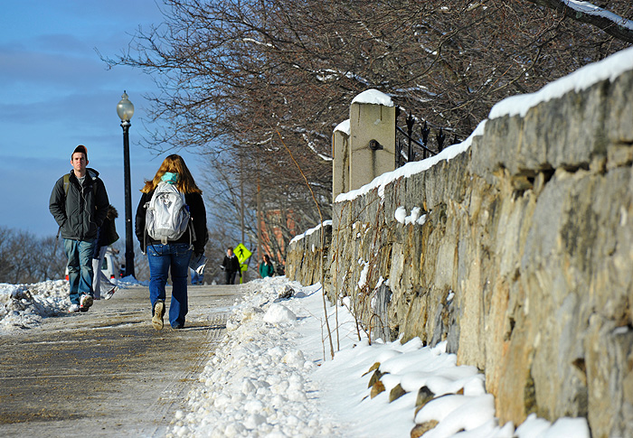 <p>Sometimes the best way to get around after a snow storm is on foot. These students take a snowy walk along North Eagleville Road near the Storrs Cemetery. Photo by Peter Morenus</p>