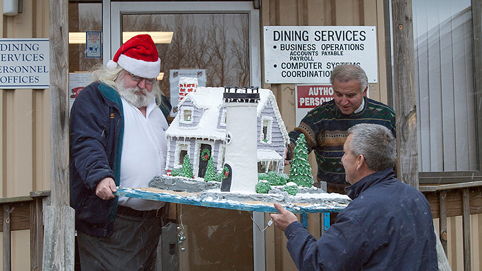 "<p>Dining Services staff (l-r) ""Santa"" David Schmidt, Tommy Assmar and Christopher Trzcinski prepare to load a gingerbread lighthouse onto the truck  for delivery to the WTIC's ""We Are The Children"" Christmas party. Photo by Jeff Gonci</p>"