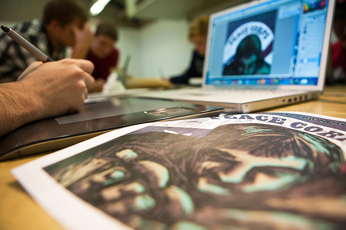 <p>Victor Preato, illustration major works on a computer illustration celebrating the 50th Anniversary of the Peace Corps. Photo by Sean Flynn</p>