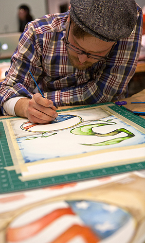 """<p>Dylan Fedora works in watercolors to create his commemorative poster which will be among those displayed on campus next spring during ceremonies observing the Peace Corps' official birthday in March.  Finished poster will all be 18"""" x 24"""", yet they are all very different in texture, design, and message.  </p>"""