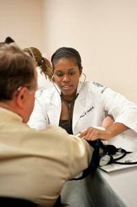 Christine Crawford, a medical student, measures the blood pressure of a visitor to a clinic held at the East Hartford Community Health Center. (Peter Morenus/UConn Health Center Photo)