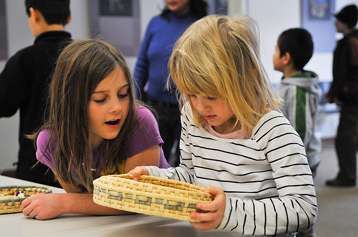 Two children attending a session on Native American Children's Games at the Connecticut State Museum of Natural History are fascinated by a hand woven basket. The session was part of a series of lectures, programs, and workshops focusing on how physical and biological processes in the environment shape play behavior. (UConn File Photo)