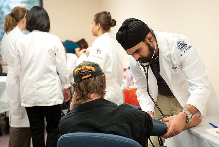 <p>Hardeep Singh, a medical school student measures the blood pressure of a visitor to a clinic held at the East Hartford Community Health Center. Photo by Peter Morenus.</p>