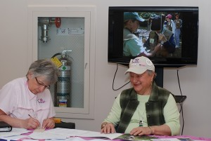Pauline Bishop from Casting for Recovery (left) and UConn Health Center Auxiliary Facilitator Irene Engel accept registrations for the Auxiliary's pig roast fundraiser at Winding Trails in Farmington April 30. (Janine Gelineau/UConn Health Center Photo)