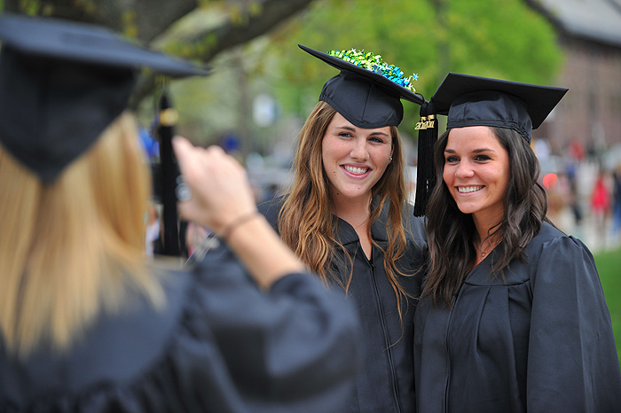 <p>Danielle Kick, left, takes a photo of Lauren Friel and Colleen Wilhide before for the second CLAS commencement ceremony held at Gampel Pavilion on May 8th. Photo by Peter Morenus</p>