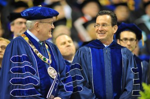 <p>The graduate commencement ceremony was held at Gampel Pavilion, where commencement speaker Gov. Dannel Malloy (right) shared a light moment with acting president Philip Austin.  Photo by Peter Morenus</p>