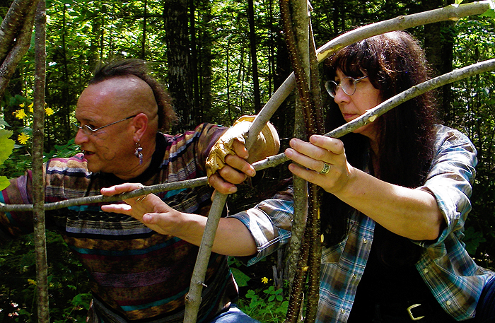Gkisedtnamoogk, left, a Wampanoag educator and Native American Studies faculty member at the University of Maine, Orono, works with Marge Bruchac to construct a wigwam frame at a site on the Penobscot River.