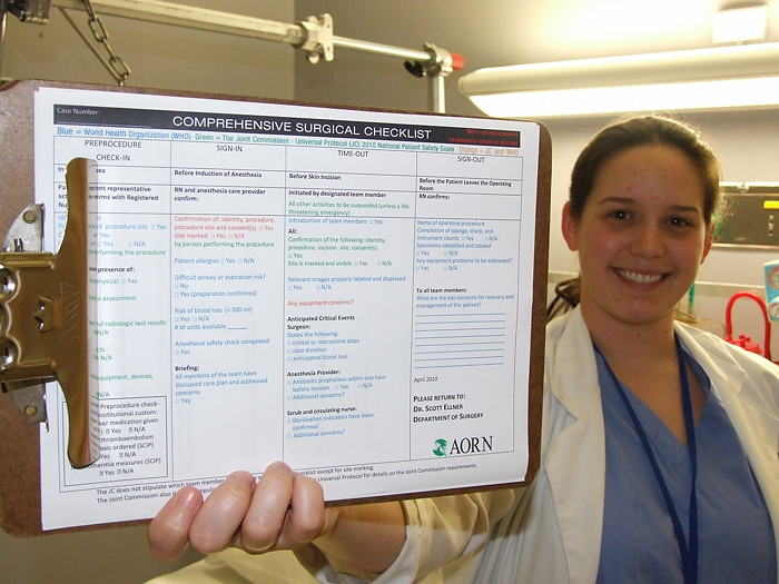 Dr. Lindsay Bliss is holding up a checklist that she designed to improve the culture of the operating room.