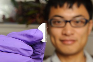 Ph.D. student Chen Jiang holds a coated sample. UConn is a leader in developing advanced thermal barrier coatings to reduce heat damage in gas turbines. (Peter Morenus/UConn Photo)