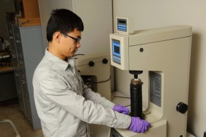 Jiang places a coated sample into a hardness tester. (Peter Morenus/UConn Photo)