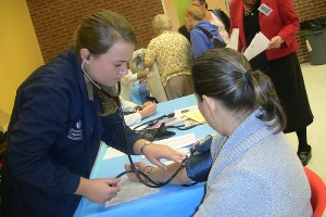 UConn nursing student monitors a patient's blood pressure at a Community Health Fair during Primary Care Week. (Photo provided by Shannon McClure)
