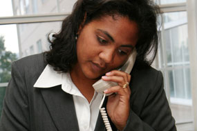 A photo of a business woman talking on the phone.