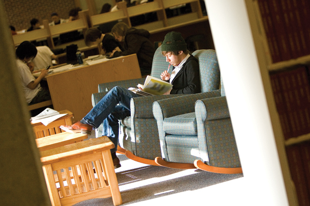 A student with a winter hat reads a book at the Homer Babbidge Library.