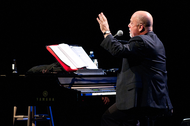 Billy Joel reviews the lyrics to his song 'Summer, Highland Falls,' while answering a question from the audience during a lecture and concert at the Jorgensen Center for the Performing Arts on Nov. 29, 2011. (Peter Morenus/UConn Photo)