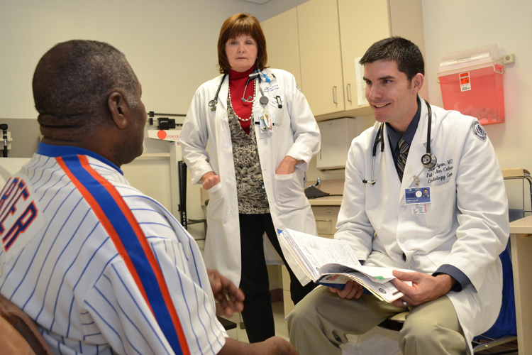 Dr. Jason Ryan and cardiology nurse practitioner Marybeth Barry talk with a patient in the Calhoun Cardiology Center.